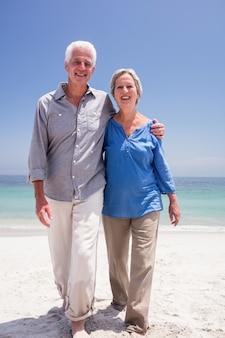 Portret van gelukkig hoger paar dat op het strand loopt