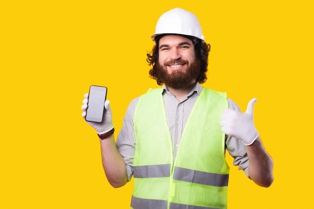 Portret van gelukkig ingenieur man met smartphone en duim omhoog gebaar tonen