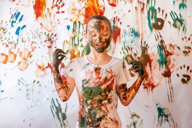 Portret van gelukkig jong kind spelen met waterverf. kindgezicht en kleding willekeurig beschilderd met verf. concept kinderplezier, kunstspelletjes en hooliganisme. kleurenafbeelding voor holi festival. ruimte kopiëren
