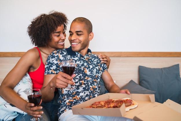 Portret van gelukkig jong latijns paar dat samen diner heeft en wijn drinkt bij hen thuis