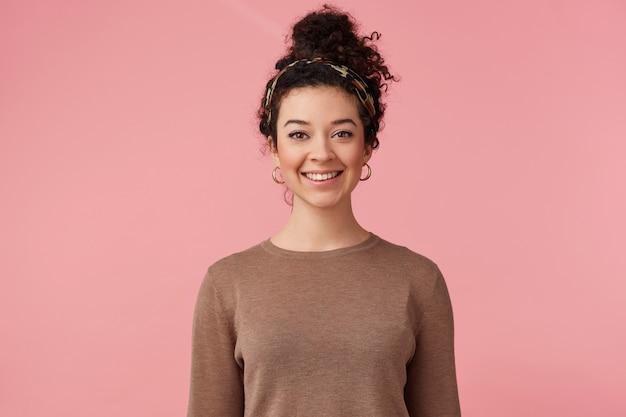 Portret van gelukkig jong mooi meisje met donker krullend haar, in grote lijnen glimlachen en kijken naar de camera geïsoleerd op roze achtergrond.