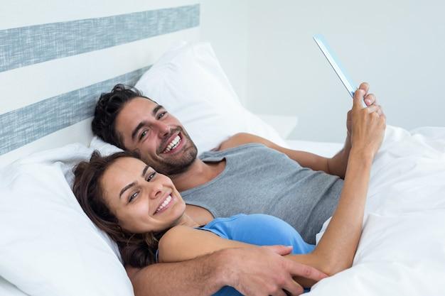 Portret van gelukkig jong paar met tablet terwijl het liggen op bed