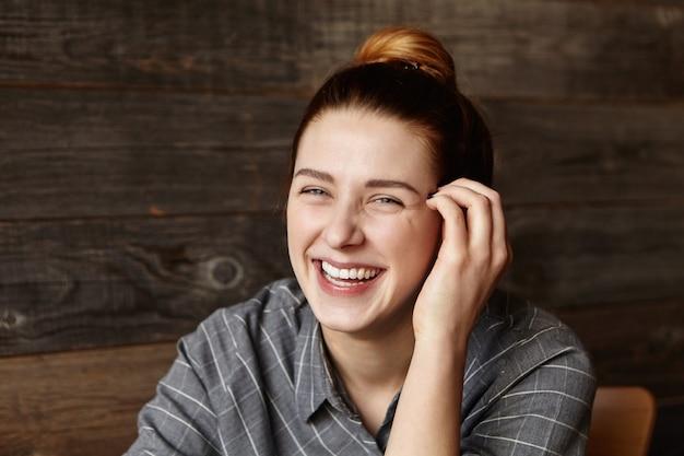 Portret van gelukkig kaukasisch meisje dat met haarbroodje camera met vrolijke glimlach bekijkt