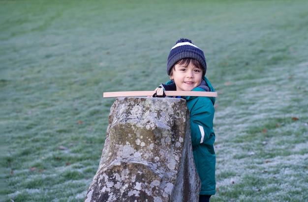 Portret van gelukkig kind met lachend gezicht staande achter oude muur met kruisboog, actieve kindjongen verstopt achter steenbaksteen schiet een speelgoedkruisboog, openluchtactiviteit tijdens koud weer winter