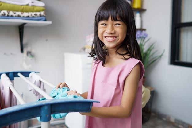 Portret van gelukkig klein aziatisch meisje die was thuis doen