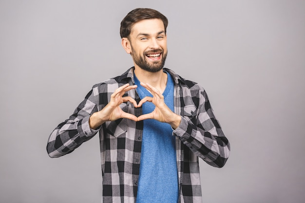 Portret van gelukkig knappe man in casual maken hart ondertekenen met vingers.