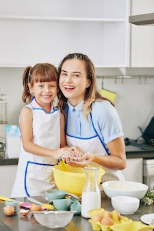 Portret van gelukkig knuffelen jonge moeder en haar preteen dochter met bloem op neuzen samen koken
