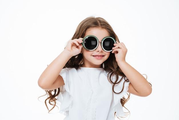 Portret van gelukkig krullend meisje in ronde zonnebril