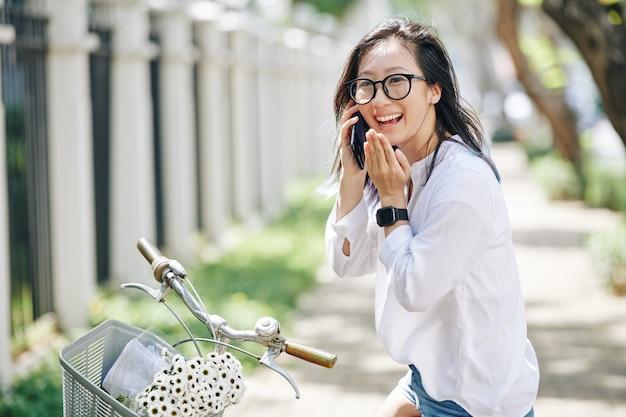 Portret van gelukkig lachen jonge chinese vrouw zittend op de fiets en praten over de telefoon met vriend of vriend