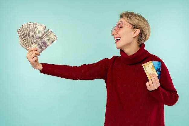Portret van gelukkig lachend blanke vrouw met creditcard en usa dollars geld terwijl kijken naar camera geïsoleerd op blauwe achtergrond.