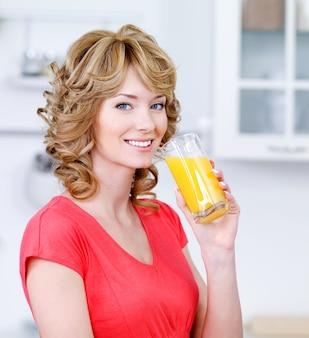 Portret van gelukkig lachend blonde vrouw vers sinaasappelsap drinken in de keuken