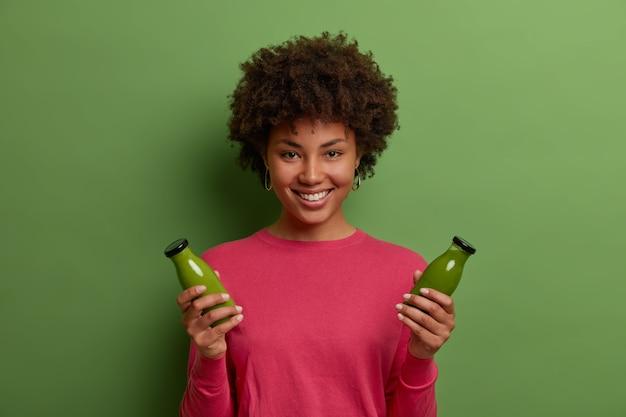 Portret van gelukkig lachend donkere vrouw heeft een gezonde natuurlijke levensstijl, houdt twee flessen groene groente smoothie, heeft de juiste voeding, geniet van een drankje van het gewichtsverlies, draagt een roze trui, glimlacht