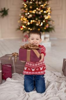 Portret van gelukkig lachend jongetje in rode gebreide trui met kerstcadeau doos in de buurt van de kerstboom. gelukkige jeugd. wachten op een kerstverhaal.