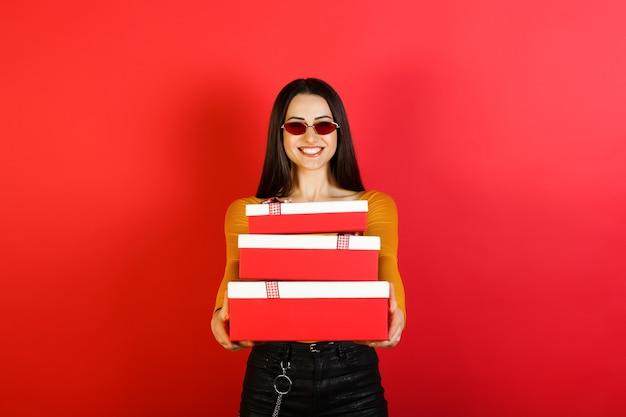 Portret van gelukkig lachend meisje in vrijetijdskleding en rode zonnebril geschenkdozen houden en glimlachen naar de camera