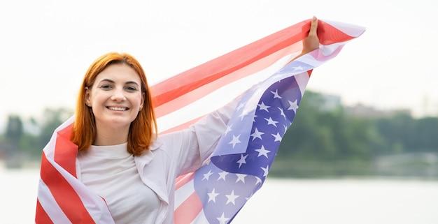 Portret van gelukkig lachend roodharig meisje met de nationale vlag van de vs op haar schouders. positieve jonge vrouw die de onafhankelijkheidsdag van de verenigde staten viert.