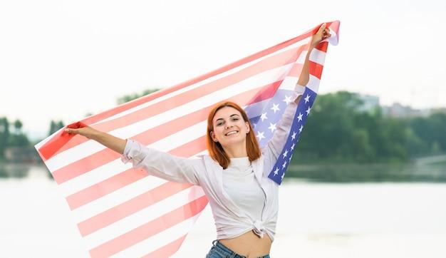 Portret van gelukkig lachend roodharige meisje met nationale vlag van de verenigde staten in haar handen. positieve jonge vrouw die de onafhankelijkheidsdag van verenigde staten vieren.