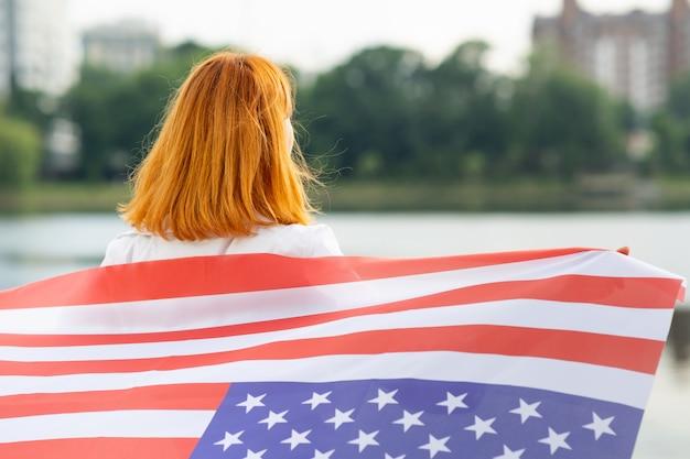Portret van gelukkig lachend roodharige meisje met nationale vlag van de verenigde staten op haar schouders