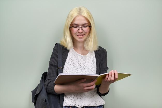Portret van gelukkig lachend student meisje tiener 16 jaar oud in bril met rugzak leerboeken kijken camera, op groene kleur achtergrond