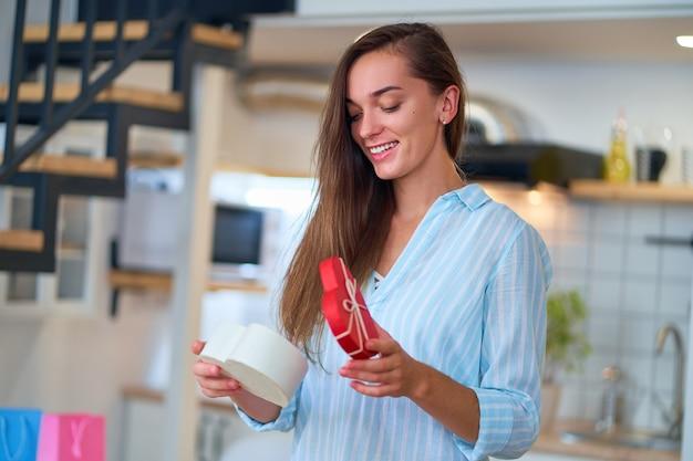 Portret van gelukkig lachend tevreden schattige geliefde verraste vrouw met een hartvormige geschenkdoos op valentijnsdag 14 februari