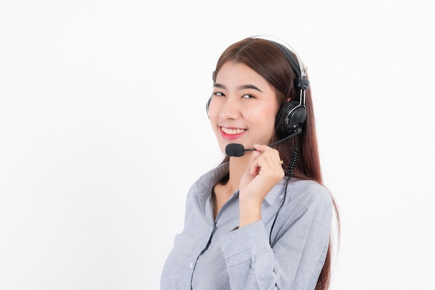 Portret van gelukkig lachend vrouwelijke klantenondersteuning telefoniste kort haar, gekleed in een grijs shirt met headset staande een kant met de oortelefoon geïsoleerd op een witte achtergrond.