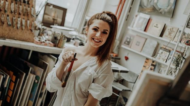 Portret van gelukkig lachend vrouwelijke kunstenaar met penseel in kunstatelier. selectieve aandacht. vintage stijl foto
