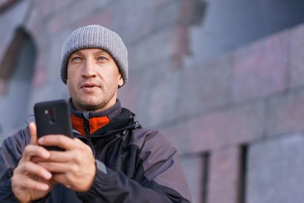 Portret van gelukkig lachende blanke man met smartphone op straat in de stad tegen bakstenen muur achtergrond...