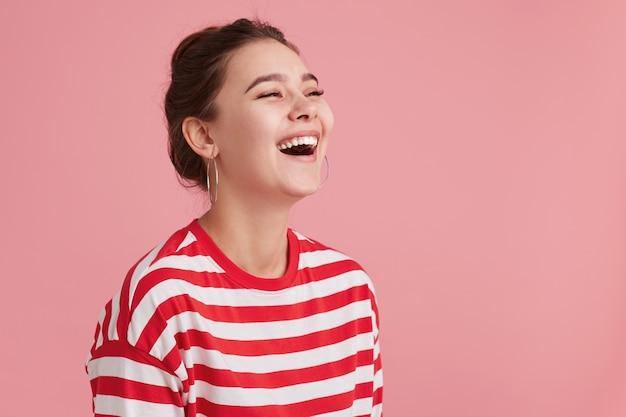 Portret van gelukkig lachende jonge vrouw met sproeten, gesloten ogen, toen ze een grappige grap hoorde