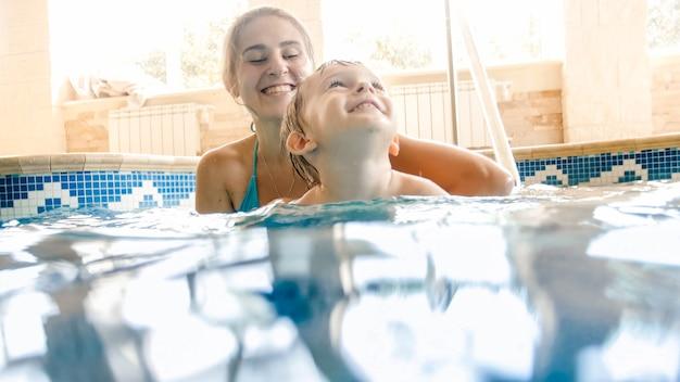 Portret van gelukkig lachende moeder met 3 jaar oude zoontje zwemmen in het zwembad op sportschool. familie ontspannen, plezier maken en spelen in het water