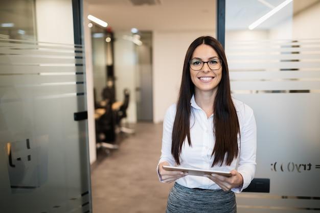 Portret van gelukkig lachende mooie zakenvrouw met tablet