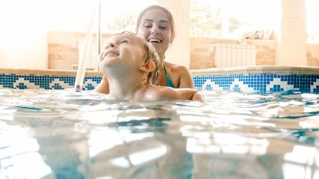 Portret van gelukkig lachende peuter jongen leren zwemmen met moeder in zwembad. familie plezier en ontspannen in het zwembad