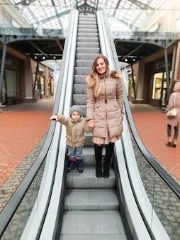 Portret van gelukkig lachende peuter jongen met mooie jonge moeder op roltrap in winkelcentrum