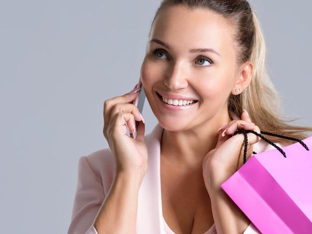Portret van gelukkig lachende vrouw met roze boodschappentas die op een mobiele telefoon spreekt.