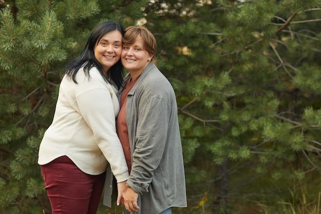 Portret van gelukkig lesbisch koppel omarmen en glimlachen naar de camera terwijl je in het bos in zomerdag staat