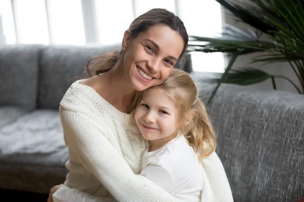 Portret van gelukkig liefhebbende alleenstaande moeder knuffelen schattige kleine dochter