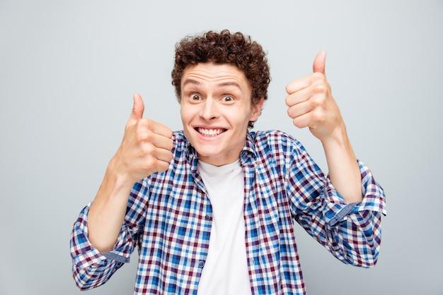 Portret van gelukkig man krullend haar stralende glimlach duim opdagen geïsoleerd op grijs