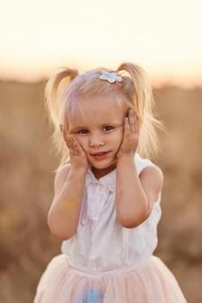 Portret van gelukkig meisje besmeurd met gekleurd poeder. klein meisje met twee staarten