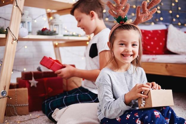 Portret van gelukkig meisje dat aanwezige kerstmis opent