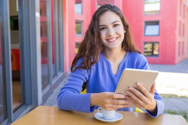 Portret van gelukkig meisje dat internet op tablet doorbladert