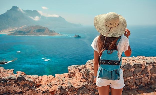 Portret van gelukkig meisje in een hoed met een rugzak staande bergen en zee. toerisme concept.