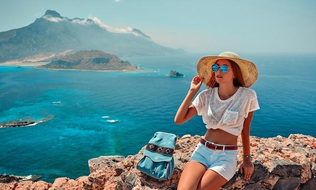 Portret van gelukkig meisje in een hoed, zonnebril en met een rugzak die bergen en overzees zitten. toerisme concept.