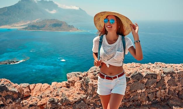 Portret van gelukkig meisje in een hoed, zonnebril en met een rugzak staande bergen en zee. toerisme concept.