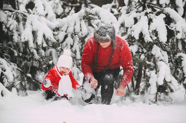 Portret van gelukkig meisje in rode laag met papa die pret met sneeuw in de winterbos hebben. meisje speelt met papa.