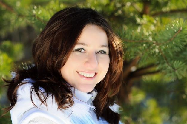 Portret van gelukkig meisje in witte winterjas en hoed dichtbij pijnboom. onscherpe achtergrond