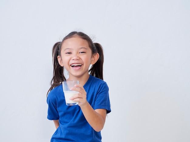 Portret van gelukkig meisje met glas melk op licht