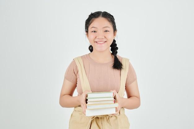 Portret van gelukkig meisje met stapel boeken geïsoleerd op lichtgrijs