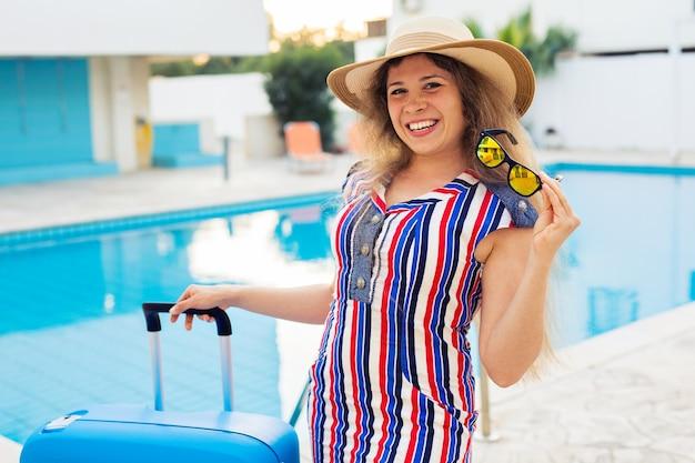 Portret van gelukkig meisje op zomervakantie tegen zwembad, gekleed gestreepte jurk en zonnebril.