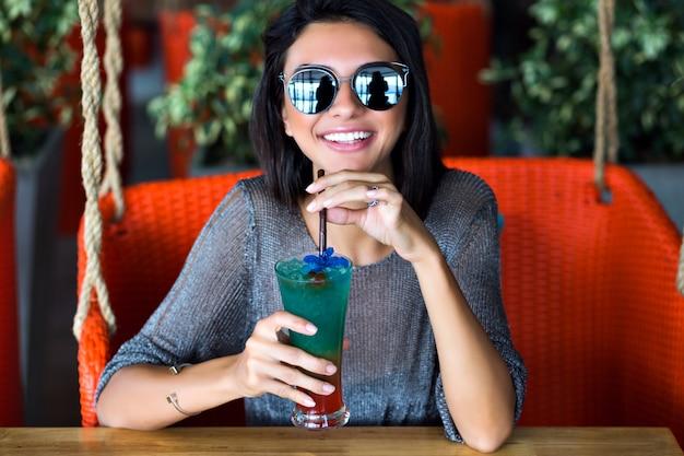 Portret van gelukkig mooie brunette vrouw drinken lekkere koude cocktail, stijlvolle outfit en gespiegelde zonnebril close-up, geniet van haar weekend, feest.