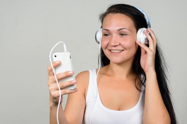 Portret van gelukkig mooie vrouw met behulp van telefoon en luisteren naar muziek