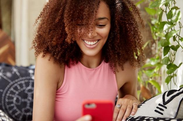 Portret van gelukkig multi-etnisch vrouwelijk model kijkt film online op moderne slimme telefoon, verbonden met draadloos internet, zit op een comfortabele bank. aantrekkelijke jonge vrouw leest nieuws van sociaal netwerk