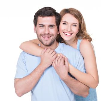 Portret van gelukkig omhelzend paar in casual - geïsoleerd